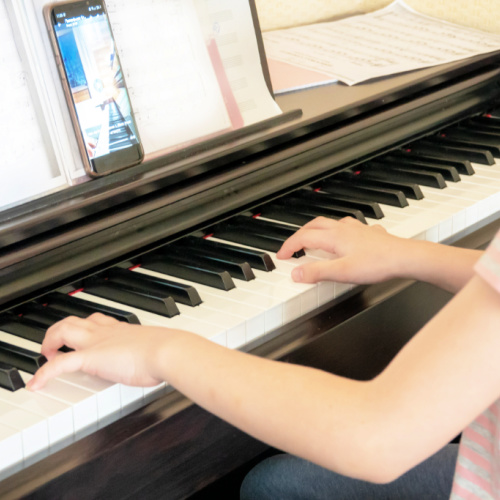 Picture of a young person participating in an online piano lesson.