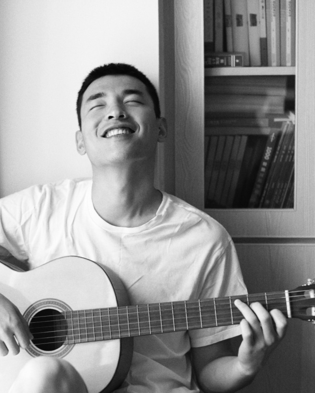 A young person playing a chord on an acoustic guitar with a smile on his face.