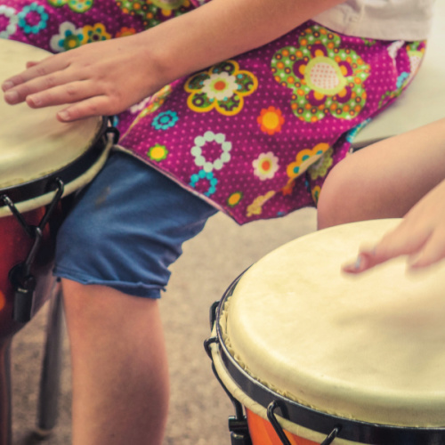 A picture of the hands of two young children playing djembe drums.