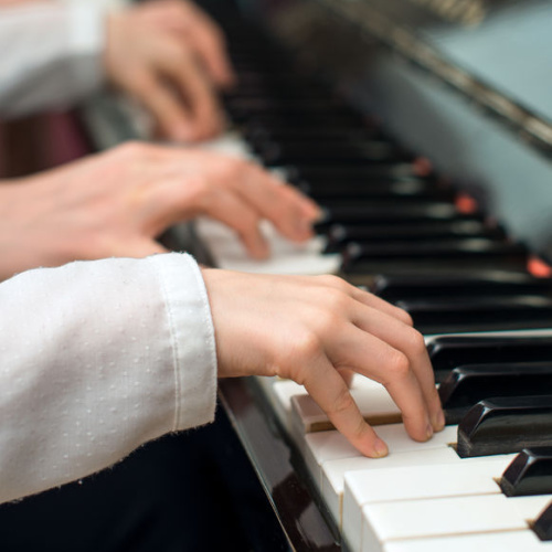 A picture of two hands pressing the keys of a piano together.
